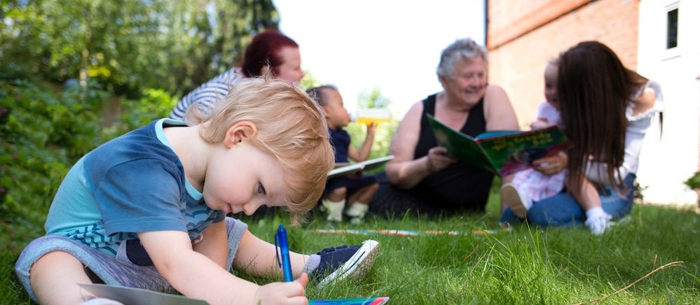 Boy writing on paper in garden with family in background, A2Dominion supported housing services